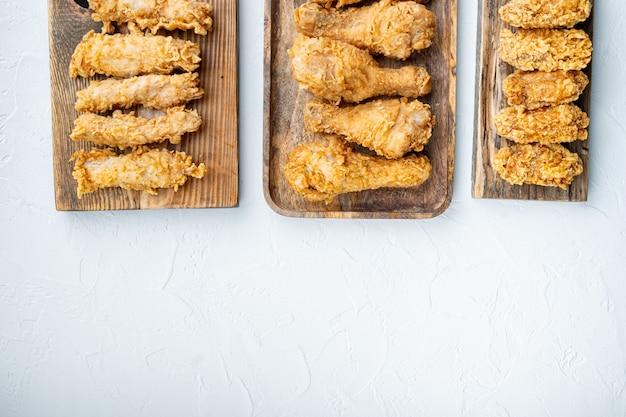 집에서 만든 바삭한 프라이드 치킨 부분은 흰색 배경, 위쪽 전망, 복사 공간이 있습니다.