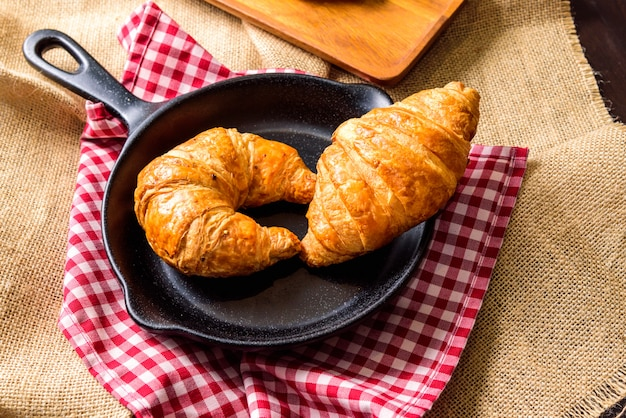 The homemade croissant is placed on a black plate shaped like a pan.