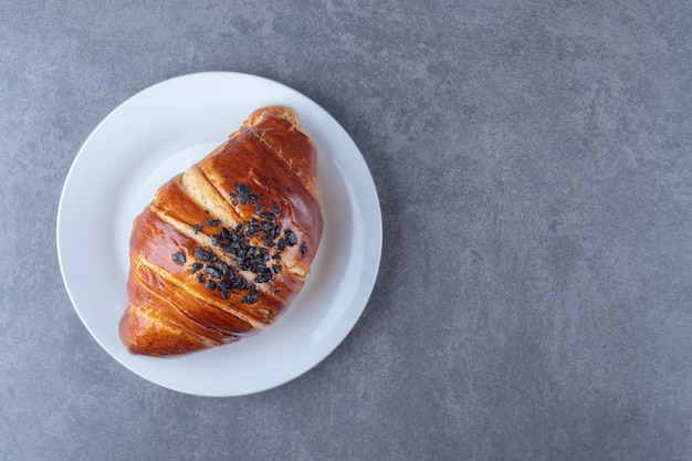 Homemade croissant with chocolate on a plate on marble table.