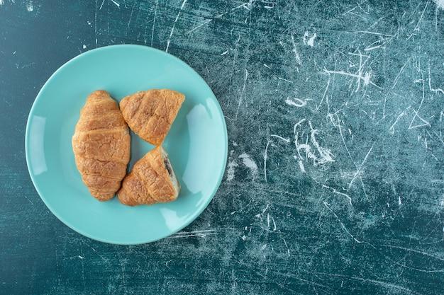 Croissant fatti in casa su un piatto, sullo sfondo blu. foto di alta qualità