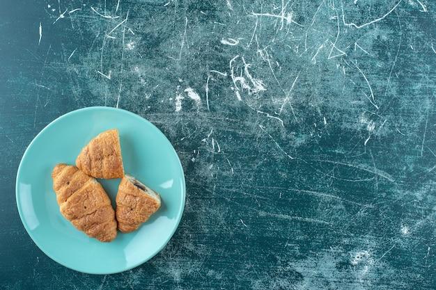 Croissant fatti in casa su un piatto, sulla superficie blu