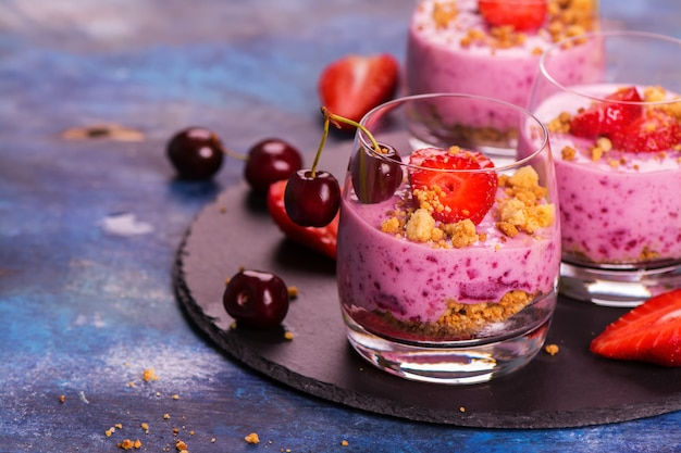 Homemade crubmle dessert with fresh berries and yogurt in glasses on wooden background