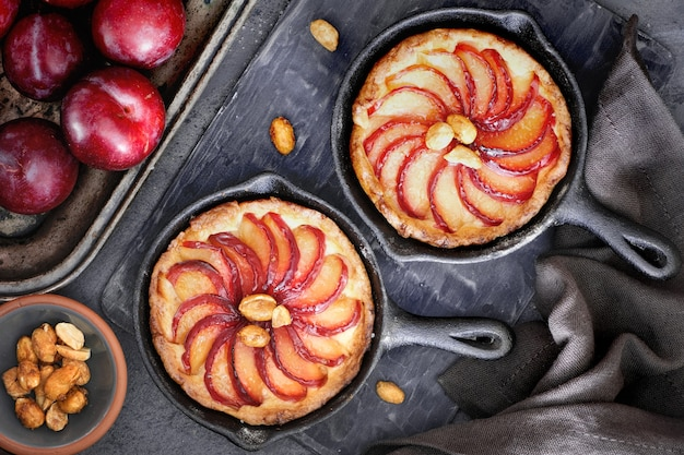 Homemade crumble tarts with plum slices baked in iron skillet