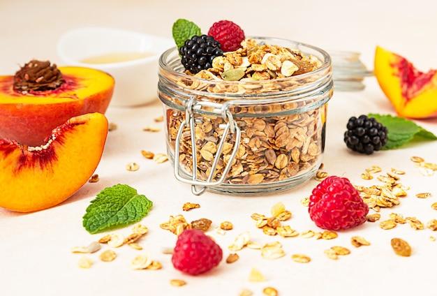 Домашняя хрустящая мюсли в стеклянной банке, персики, ягоды, мед и мята. здоровая веганская или вегетарианская закуска.