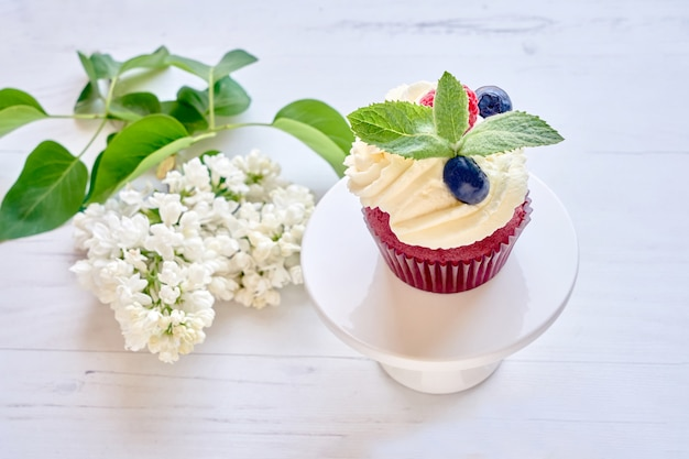 Homemade cupcake decorated with white cream and berries on cakestand on white table.