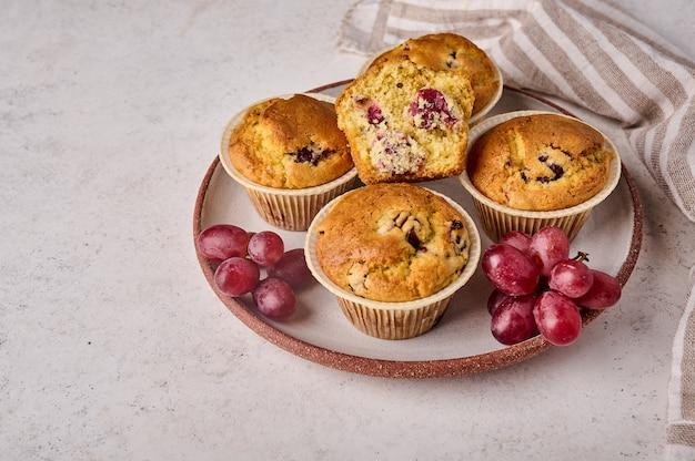 明るい背景にナプキンとプレートにさくらんぼとブドウの自家製カップケーキをクローズアップ