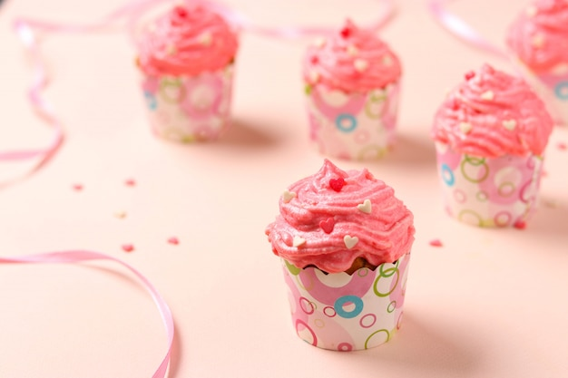 Homemade cupcakes with cream on a pink