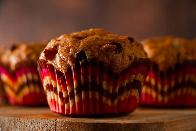 건포도와 함께 홈메이드 컵 케이크입니다. 나무 배경에 전통적인 가을 파이입니다.