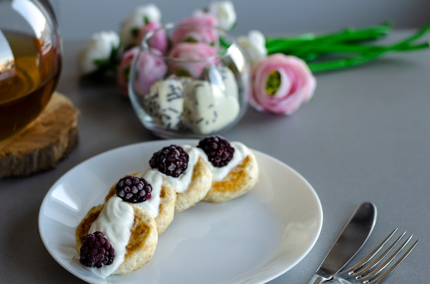 Homemade curd cheese pancakes with sour cream and blackberries for breakfast.