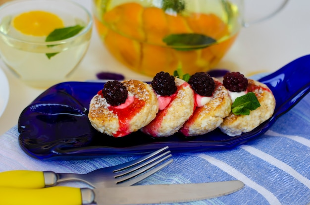 Homemade curd cheese pancakes with sour cream and blackberries