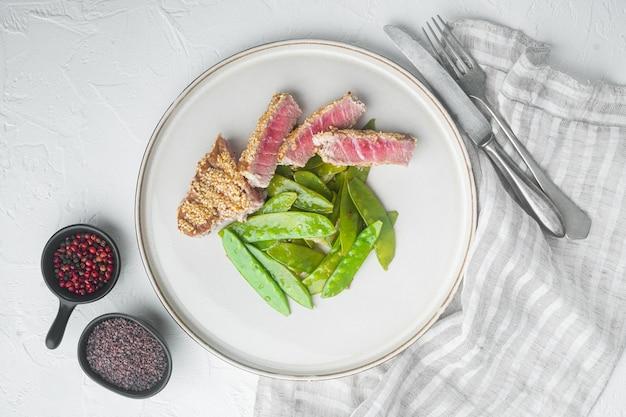 흰 돌에 접시에 봄 양파와 설탕 스냅 완두콩으로 만든 집에서 잘라 구운 참깨 참치 스테이크 세트