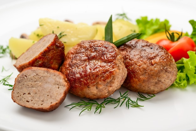 Homemade cutlets with potatoes and vegetables on a white background.