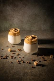 暗い背景に自家製ダルゴナコーヒー。コーヒー豆とサトウキビの隣。