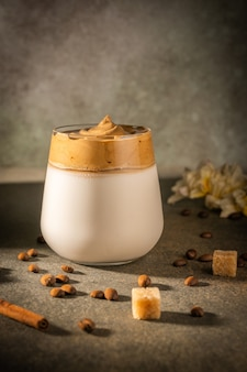 Домашний кофе dalgona на темном фоне. рядом с кофейными зернами и тростниковым сахаром.