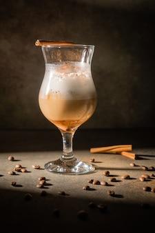 暗い背景に自家製ダルゴナコーヒー。コーヒー豆とシナモンスティックの隣。