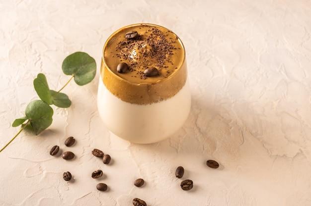 明るい背景に自家製ダルゴナコーヒー。コーヒー豆の隣と葉のある枝。
