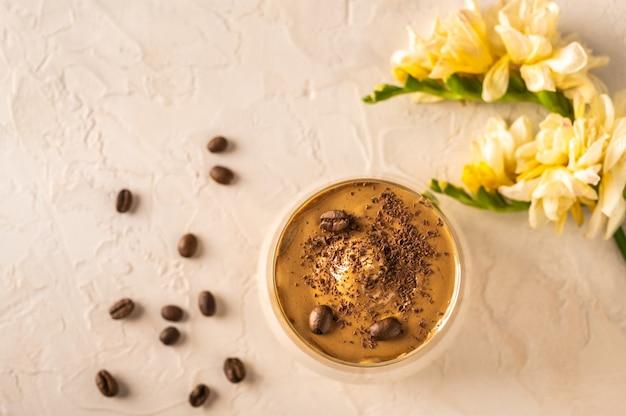 明るい背景に自家製ダルゴナコーヒー。コーヒー豆と花の隣。