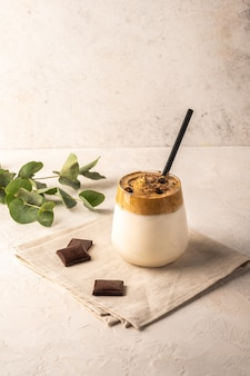 Homemade dalgona coffee with chocolate on napkin on light background.