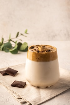明るい背景のナプキンにチョコレートと自家製ダルゴナコーヒー。