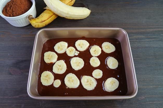 Homemade dark chocolate banana cake batter in cake pan with baking ingredients on wooden table
