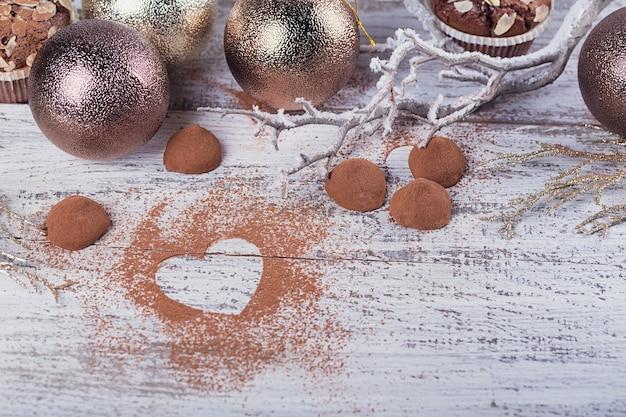 白い素朴な木製のテーブルにハート型のココアパウダーと冬の装飾が施された自家製ダークチョコレートトリュフ。冬の休日の背景。テキスト用のコピースペースを備えたフラットレイ。