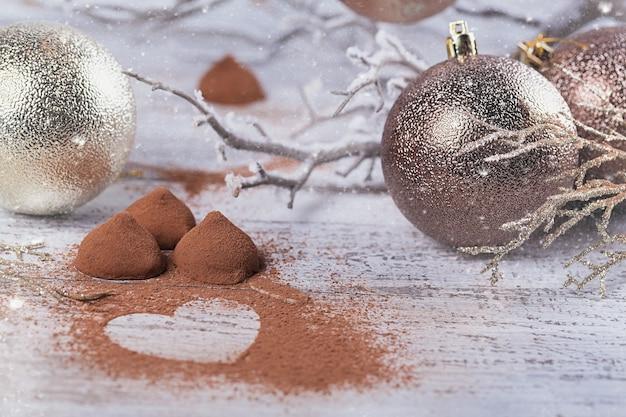 白い素朴な木製のテーブルにハート型のココアパウダーと冬の装飾が施された自家製ダークチョコレートトリュフ。冬の休日の背景。