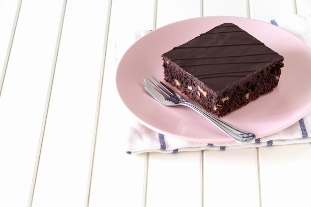 Homemade dark chocolate vegan brownie cake with nuts pink plate white background.