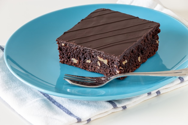 Homemade dark chocolate vegan brownie cake with nuts plate light background. selective focus.