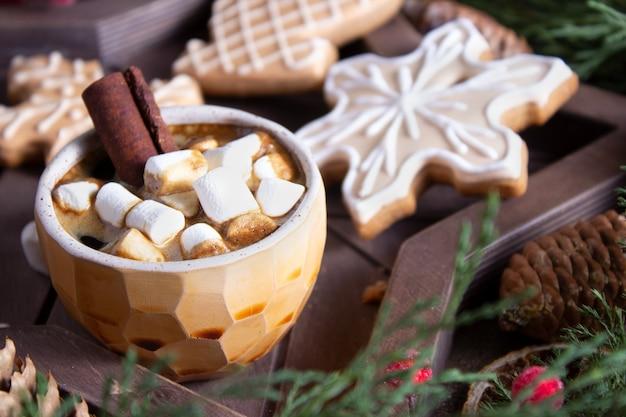 ホットチョコレートとマシュマロを添えた自家製の装飾されたジンジャーブレッドクッキー