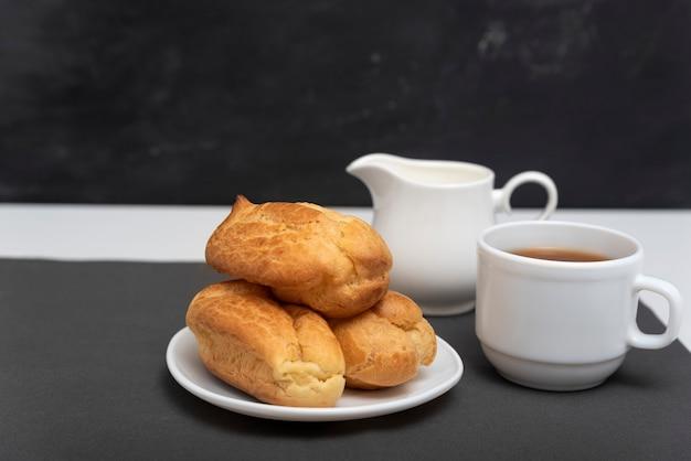Домашние нежные профитроли и чашка кофе. традиционные французские эклеры. вид сбоку.