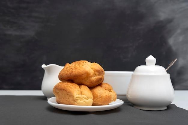 Домашние нежные профитроли на столе, чашка чая. традиционные французские эклеры. серая поверхность.