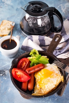 Homemade delicious american breakfast with fried egg, toast, sausage, vegetable, black coffee