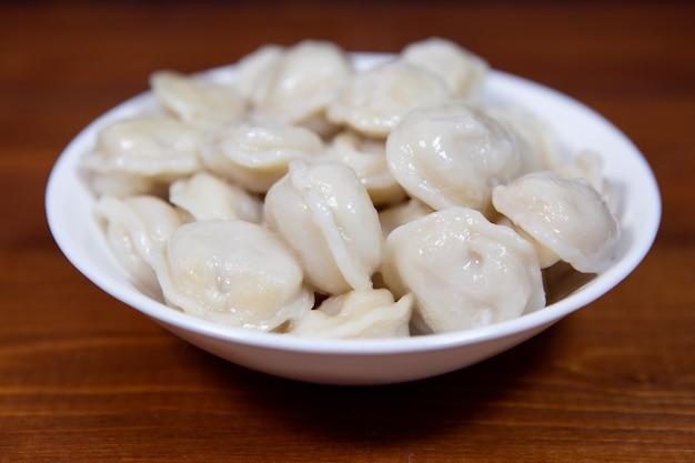 木製のテーブルの上の白いプレートに自家製のおいしいゆで餃子