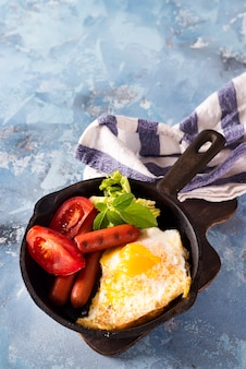 Homemade delicious breakfast on a pan with fried egg, toast, sausage, vegetable, black coffee