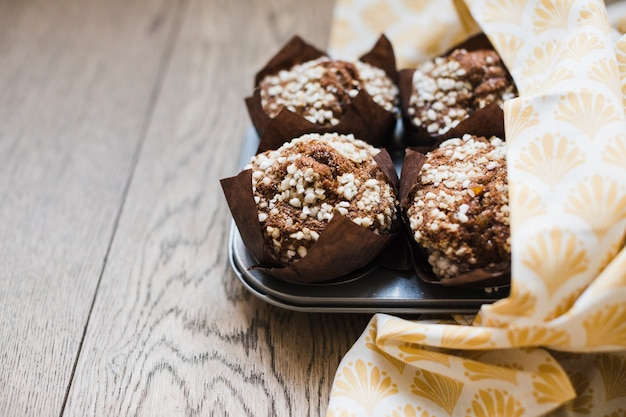 Homemade delicious chocolate muffin in brown paper on baking tray