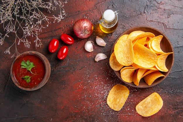 Deliziose patatine croccanti fatte in casa all'interno e all'esterno della bottiglia di olio marrone ketchup pomodori aglio cipolla su sfondo scuro