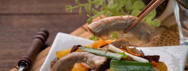 Домашняя вкусная еда с черным грибком и зеленым луком на деревянном столе
