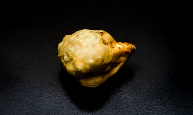 A homemade delicious fried samosa on a textured dark background