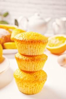 白いテーブルの上に自家製のおいしいレモンマフィンカップケーキ。上面図。