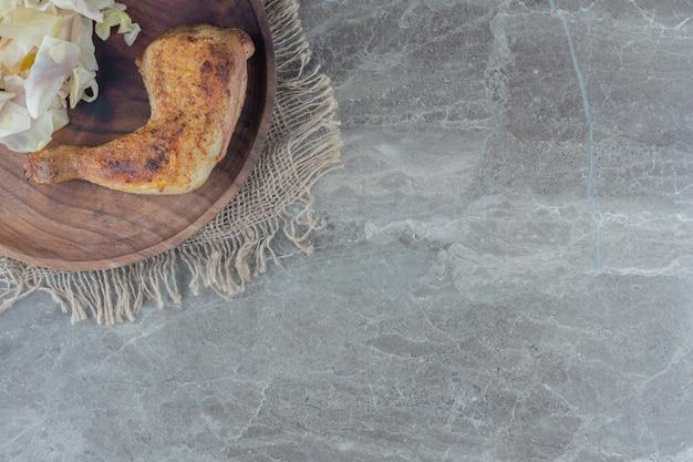 Домашний вкусный обед. жареные куриные голени и квашеная капуста на деревянной тарелке.