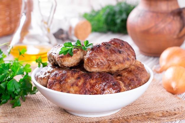 Домашние вкусные мясные котлеты в тарелке на столе