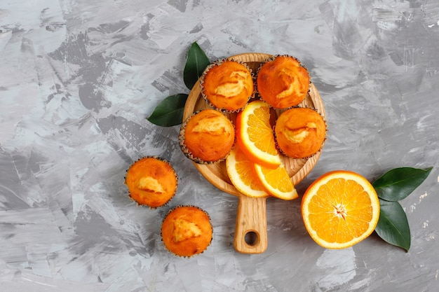 Homemade delicious orange muffins with fresh oranges.