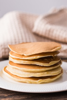 Домашние вкусные блины на белой тарелке. концепция завтрака.