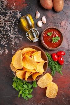 Patatine fritte deliziose fatte in casa in una piccola ciotola marrone patate olio bottiglia pomodori verdi aglio e ketchup sul tavolo scuro