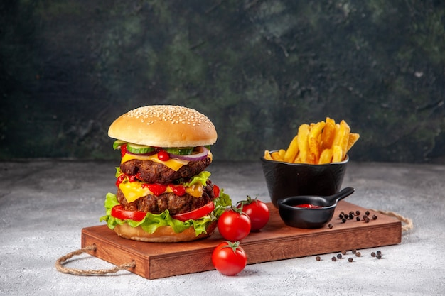 Deliziose patatine fritte fatte in casa al pepe con ketchup di pomodori e panino sul tagliere