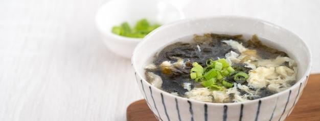 明るい木製のテーブルの背景の上にボウルに自家製のおいしい海藻の卵のドロップスープ。
