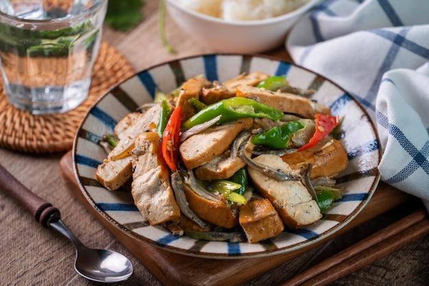 Самодельный вкусный жареный сушеный бобовый творог с сушеной рыбой и зеленым чили на фоне деревянного стола.