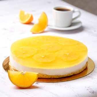 Homemade delicious sweet passion fruit orange cake, mousse dessert on cup of coffee americano