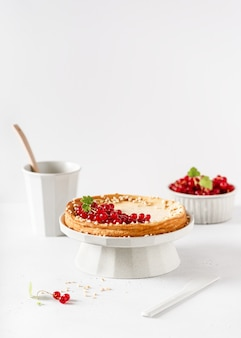 Homemade delicious vanilla cheesecake decorated with fresh red currant berries.