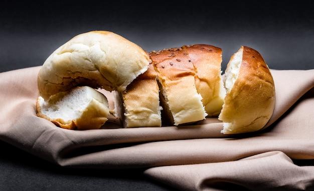 自家製のおいしい小麦パンは、粗い暗い背景の上の茶色の布の上のビューをクローズアップ